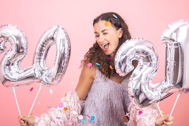 Linda morena festeira com cabelos cacheados e roupas festivas, posando em um fundo rosa do estúdio com confetes e segurando balões prateados para o conceito de ano novo