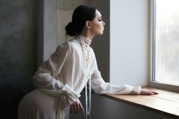 Linda morena garota esbelta, sentado no sofá em um vestido longo branco. retrato de uma mulher com uma joia no pescoço. penteado perfeito e cosméticos da mulher, nova coleção de vestidos leves