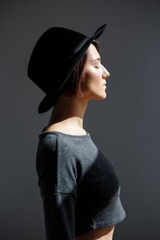 Linda morena jovem de chapéu preto em pé no perfil.