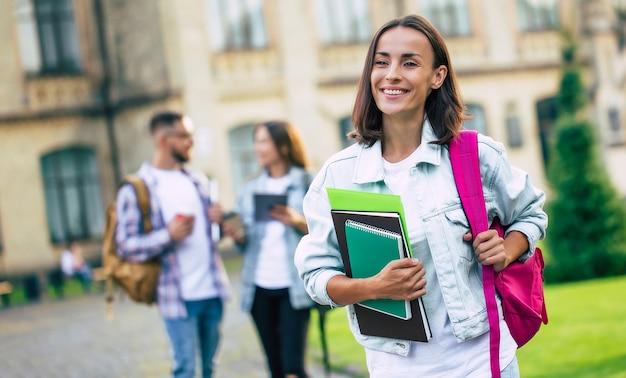 Linda morena jovem estudante em roupas jeans com mochila e livros nas mãos está de pé sobre um grupo de seus amigos estudantes