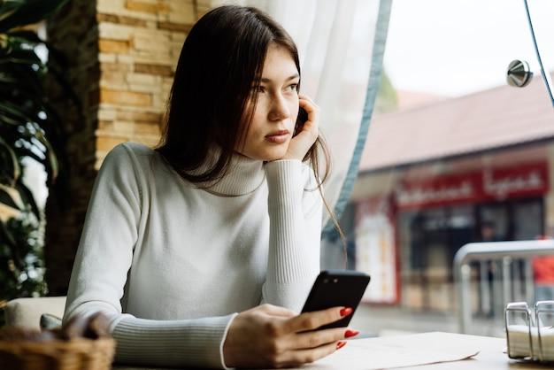 Linda morena jovem sentada em um café, olhando pensativamente pela janela, segurando um smartphone
