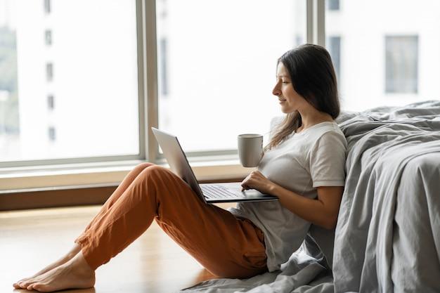 Linda morena jovem trabalhando em um laptop e bebendo café, sentada no chão perto da cama pela janela panorâmica, com uma bela vista do andar alto. compras na internet.