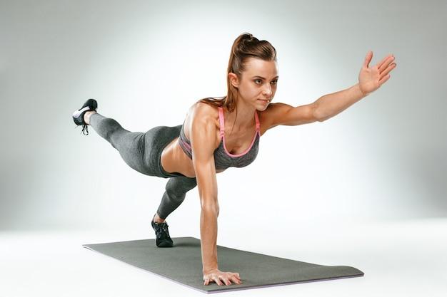 Linda morena magra fazendo algumas flexões na academia