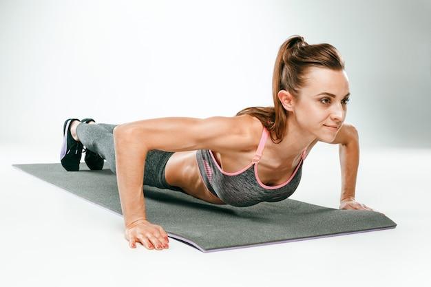 Linda morena magro fazendo algumas flexões no ginásio