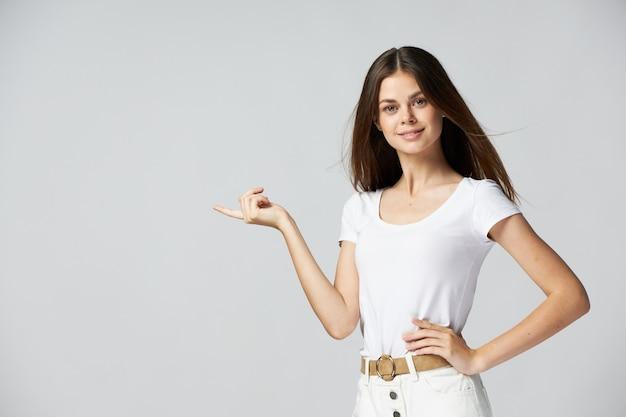 Linda morena mostra o dedo para o lado da camiseta branca cortada luz