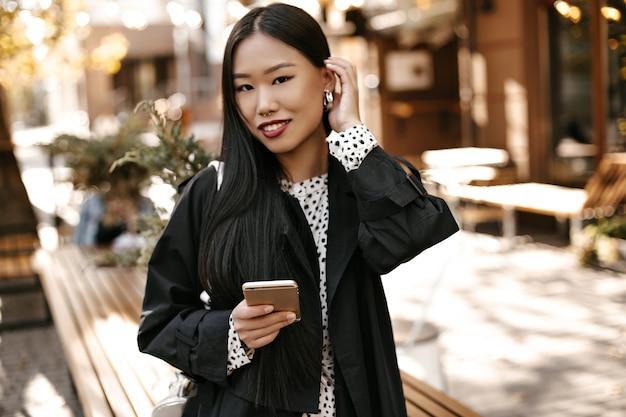 Linda morena mulher asiática em trincheira preta sorrindo sinceramente