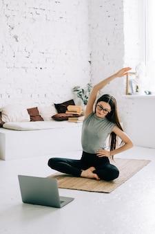 Linda morena mulher fitness fazendo exercícios de alongamento
