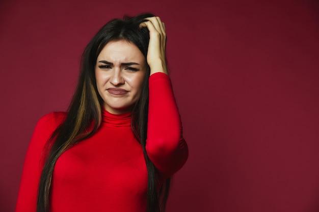 Linda morena perplexa caucasiana garota vestida de camisola vermelha está raspando o cabelo dela