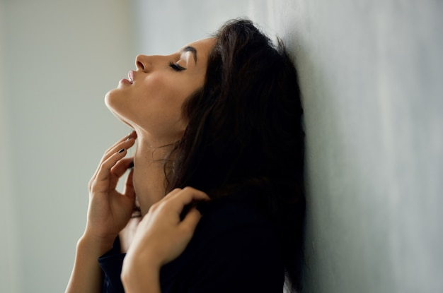 Linda morena perto da janela com um vestido preto posando de modelo de luxo