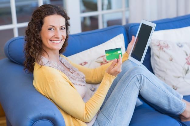 Linda morena relaxando no sofá com tablet