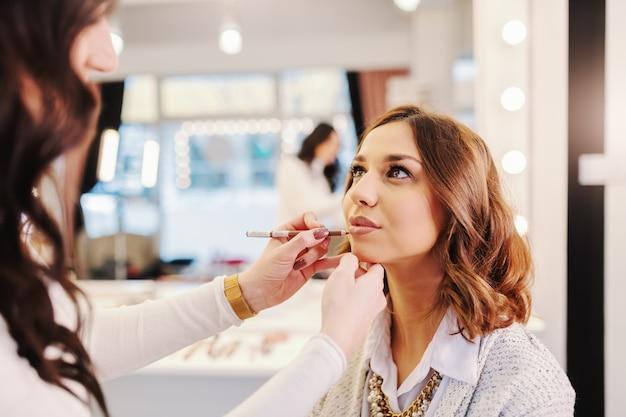 Linda morena sentada no salão de beleza enquanto maquiador colocando lápis de cera nos lábios.