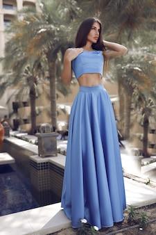Linda morena sexy em pé perto da piscina no vestido longo azul separado, mulher com cabelos longos, corpo perfeito e rosto bonito, maquiagem, sob as palmeiras