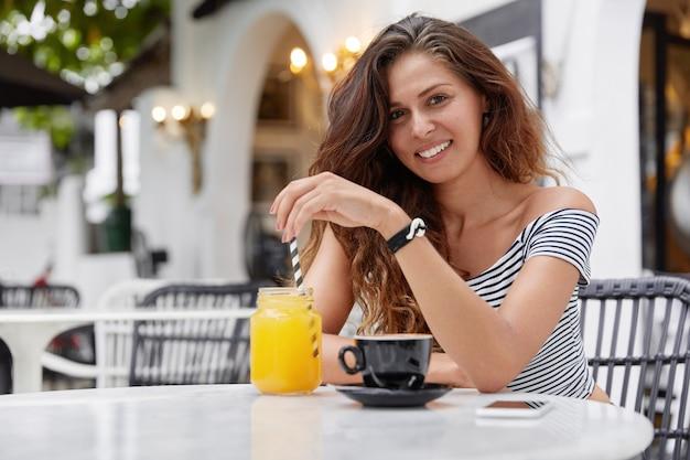 Linda morena sorridente mulher bebe suco ou café, passa o tempo livre em restaurante
