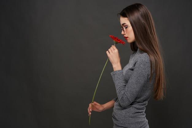 Linda morena usando óculos escuros glamour vermelho flor maquiagem estúdio