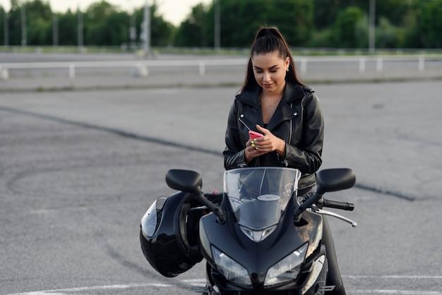 Linda motociclista sorridente usa smartphone enquanto está sentado em uma motocicleta esporte elegante no estacionamento urbano ao ar livre.