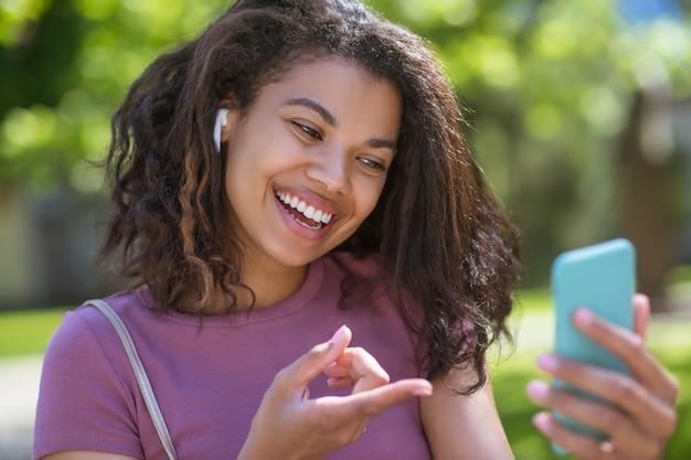 Linda mulata falando ao telefone e sorrindo