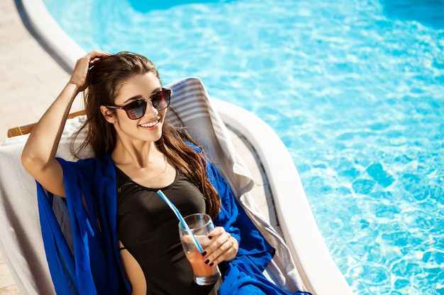 Linda mulher a beber cocktails, deitada na espreguiçadeira perto da piscina