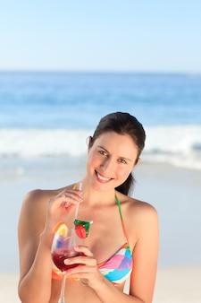 Linda mulher a beber cocktails na praia