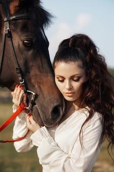 Linda mulher acaricia um cavalo e detém o freio em um campo