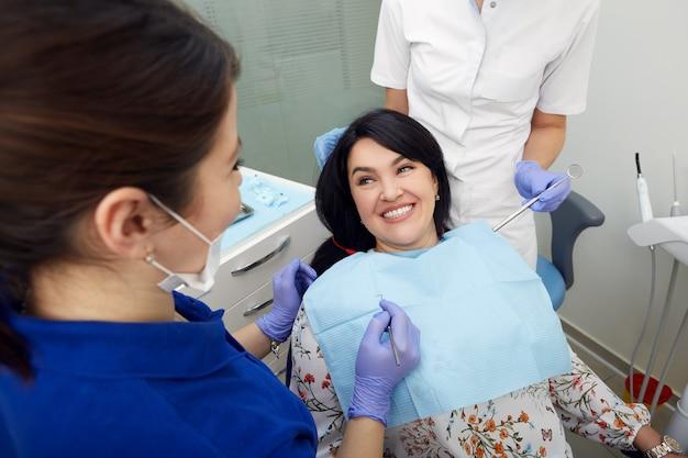 Linda mulher adulta alegre fazendo exame de dente no consultório odontológico