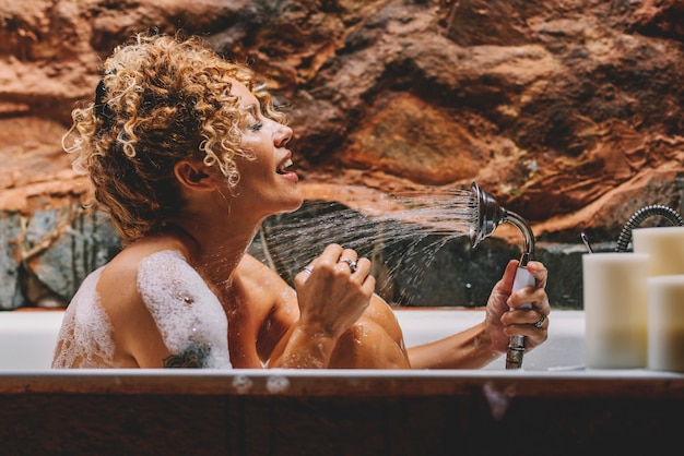 Linda mulher adulta cantando no chuveiro em casa no banheiro tendo cuidado e relaxe. cuidar do corpo positivamente e mulheres felizes e relaxadas tomando banho com água e sabão em bolhas