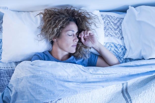 Linda mulher adulta caucasiana solitária dormindo sozinha em uma cama de casal em casa