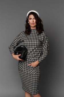 Linda mulher adulta com maquiagem suave, usando um vestido xadrez, segurando uma bolsa preta e posando contra uma superfície cinza