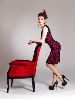 Linda mulher adulta com penteado fashion e poltrona vermelha posa no estúdio