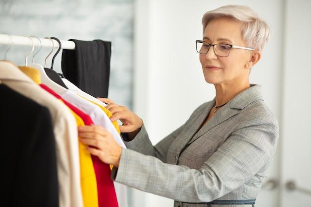 Linda mulher adulta de terno escolhe roupas
