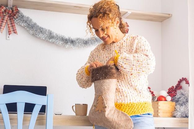 Linda mulher adulta decorar a casa com decoração de férias de natal, como meias e bolas. conceito de pessoas aproveitando a temporada de natal interior. mulher feliz em atividade de lazer indoor