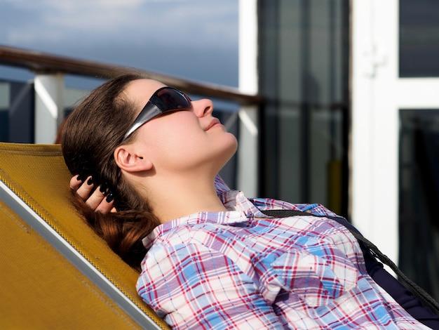 Linda mulher adulta descansando na espreguiçadeira no convés de um navio de cruzeiro