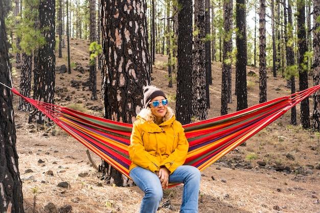 Linda mulher adulta desfruta de bosques florestais relaxando sentado em uma rede sozinha na independência alternativa atividade de lazer ao ar livre e férias - sentimento de pessoas e meio ambiente