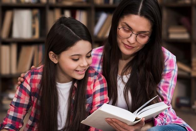 Linda mulher adulta e jovem lendo um livro