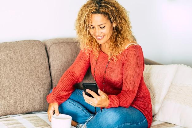 Linda mulher adulta em casa com telefone e relaxa com atividades de lazer sentada no sofá