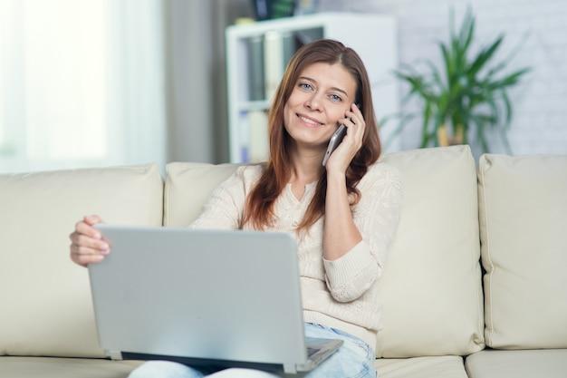 Linda mulher adulta em casa falando com o celular no sofá com o laptop