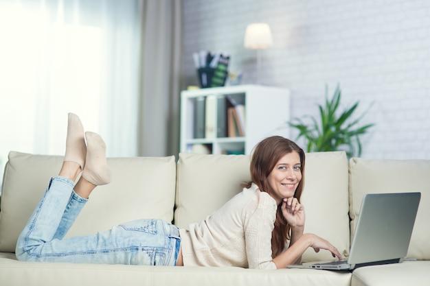 Linda mulher adulta em casa no sofá com o laptop
