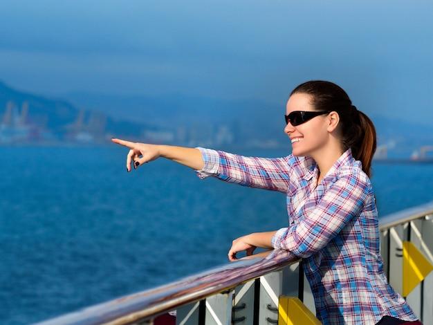Linda mulher adulta em pé no convés de um navio de cruzeiro e apontando para algo