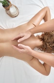 Linda mulher adulta em salão de spa com massagista profissional.