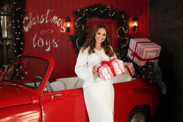 Linda mulher adulta em um vestido de malha branco sorri com um presente de natal nas mãos, ao lado de um carro retrô vermelho.