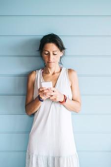Linda mulher adulta encostada em uma parede de madeira enquanto estiver usando um smartphone