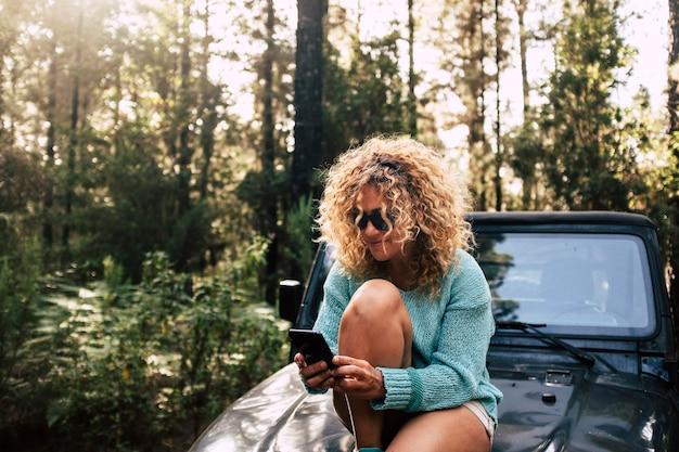 Linda mulher adulta livre senta-se no nariz do carro e usa a conexão de tecnologia de celular no meio da floresta