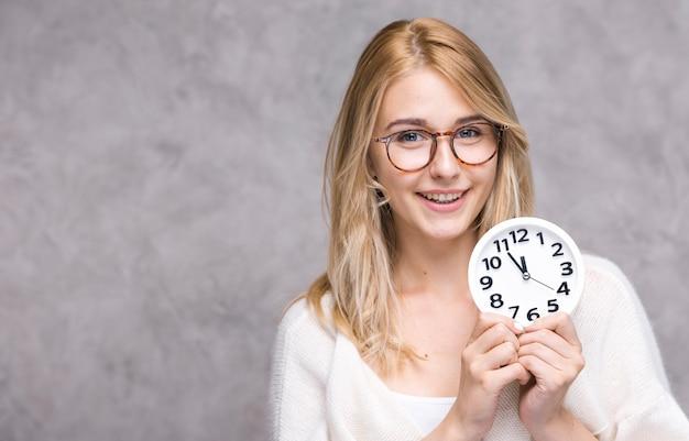 Linda mulher adulta segurando o relógio
