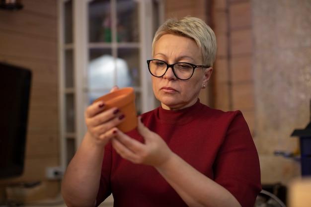 Linda mulher adulta segurando um pote de cerâmica de barro nas mãos