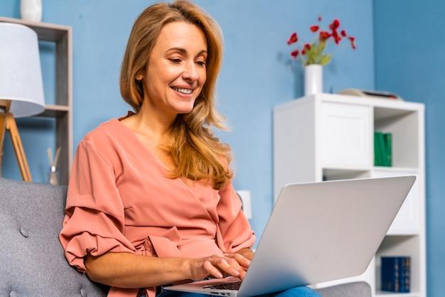 Linda mulher adulta sentada sozinha em casa e trabalhando em um computador laptop