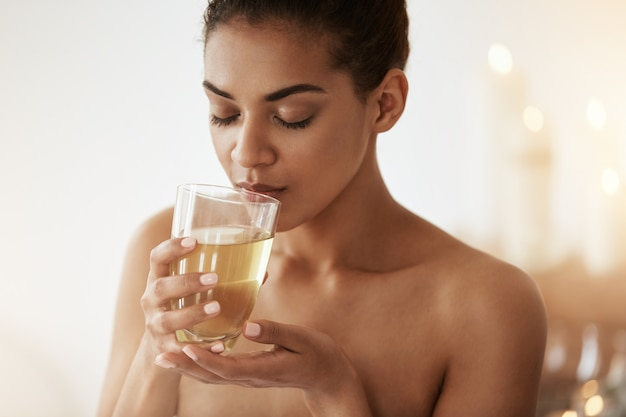 Linda mulher africana bebendo chá sorrindo relaxante no salão spa.