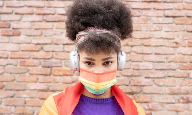 Linda mulher africana com a bandeira do orgulho gay e fones de ouvido na cidade