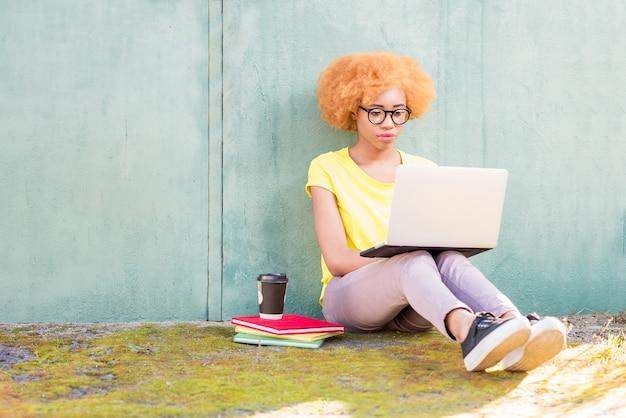 Linda mulher africana com cabelo encaracolado, estudando com laptop e livros sentados ao ar livre no fundo da parede verde.