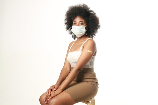 Linda mulher africana com máscara médica após a injeção da vacina