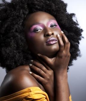 Linda mulher africana com um grande cabelo afro encaracolado e flores no cabelo