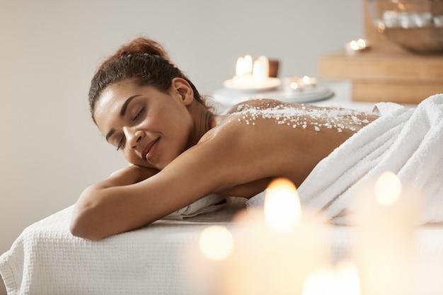 Linda mulher africana descansando relaxante com sal marinho nas costas no salão spa.